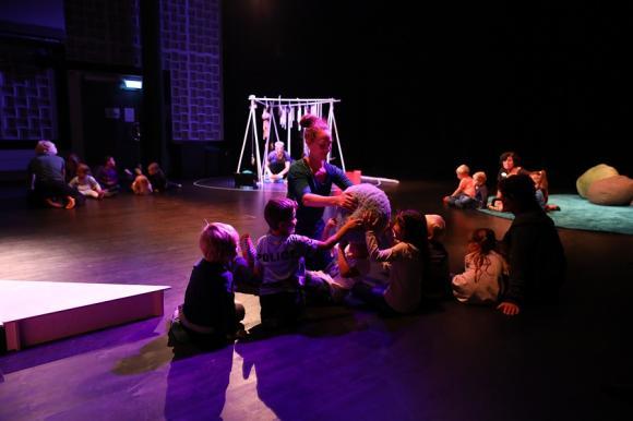 Publiken sitter med i ö-landskapet som byggts upp på Stora scenen i Kulturhuset.