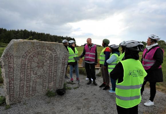 Pelle och Lotta i rosa västar har som volontärer varit med som cykelinstruktörer under kursen. Här berättar Pelle om Brostenen för cyklisterna.