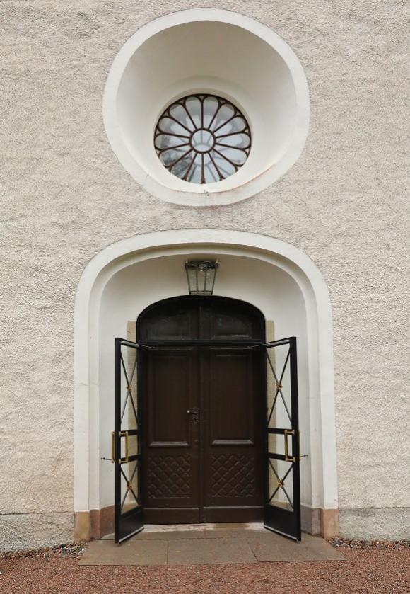 Kyrkporten är redo för biskopen. Innanför porten är kyrkan fylld till bristningsgränsen med nyfikna församlingsmedlemmar.