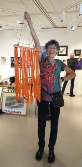 Mona visar upp en av årets nyheter: mobilerna som ska visa besökarna att de kommit rätt, till en av Konstrundans utställninglokaler.
