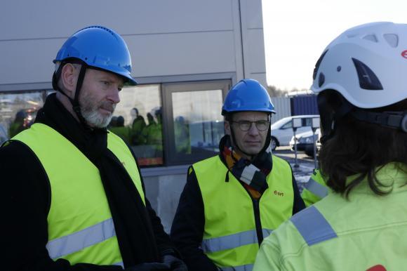 Fredrik Kjos, kommunstyrelsens ordförande i Upplands-Bro, och Ulf Kristersson, Moderaternas partiledare,lyssnar till E.ON:s regionchef Lena Berglund, under besöket på E.ons fjärrvärmeanläggning i Högbytorp.