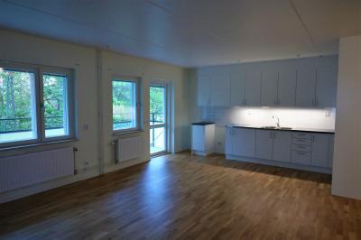 Kök och vardagsrum i öppen planlösning. Utanför skymtar den stora balkongen. Just det här är en trea. Lägenheterna har genomgående ekparkett och vitmålade väggar.