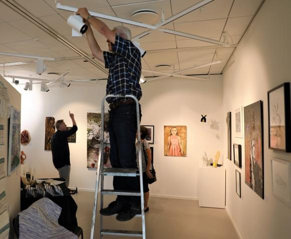 Lasse försöker ställa in trilskande ljuskällor medan Claes och Marianne tittar på vilka som lyser och vilka som behöver bytas ut eller justeras.