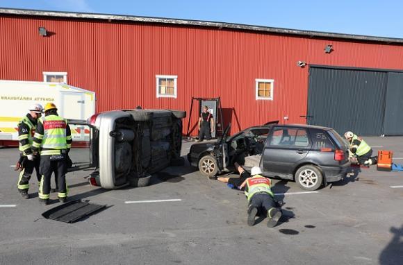 HLR har tagits över av en av brandmännen medan en annan ligger på marken och fixerar nacken på föraren i bil 1. Under tiden som alla verktyg och all utrustning för en klippning dukas fram resonerar brandmännen om hur de ska komma åt de skadade i olycksbil 2.