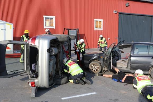 Febril aktivitet råder. Nästa del i säkerhetsarbetet är att säkra den välta bilen så att den inte tippar när brandmännen börjar jobba med att få ut de skadade.