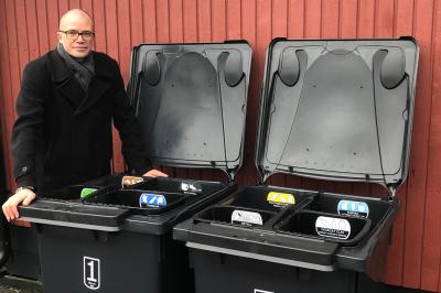 Upplands-Bro kommuns avfallschef, Mikael Thelin, demonstrerar kommunens nya fyrfackssopkärl som kommer att göra det enklare för kommunens invånare att sortera avfall.