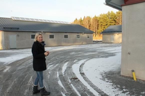 Anna Fischer vid ett av gårdstunen. Stallen är uppbyggda med gårdsplan i mitten och ett \