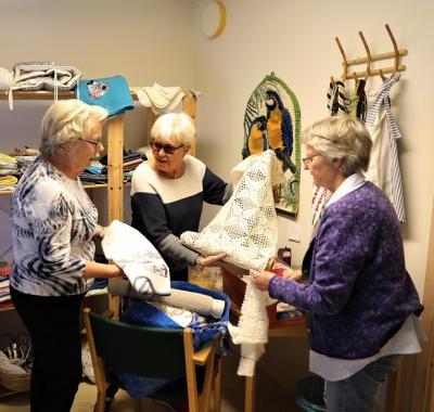 Maj-Britt, Lisbeth och Marianne går igenom en nyinkommen gåvopåse med dukar och tyger. Nytvättat, manglat och exemplariskt hopvikt.