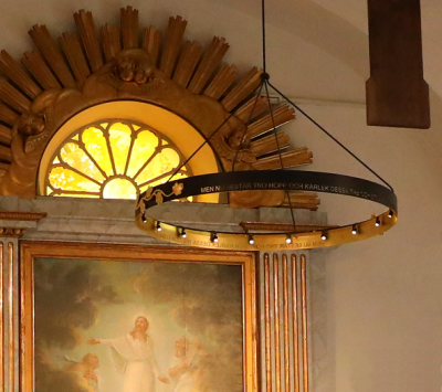Den nya ljuskronan framme vid altaret har en inskription som lyder: MEN NU BESTÅR TRO, HOPP OCH KÄRLEK DESSA TRE OCH STÖRST AV ALLT ÄR KÄRLEKEN.