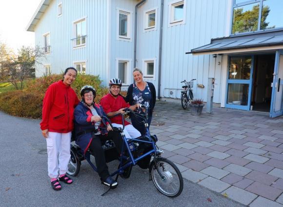 Elisabet och Ezadin ska ut på en cykeltur.Saowanee hjälper till med bälte, pedalspännen och cykelhjälm. Längst till vänster står Susanna kraftelid,enhetsledare på Allégården.