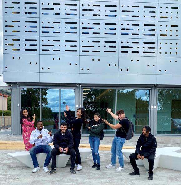 Hanna Rydstedt och Sharmarke Elmi utanför sporthallen tillsammans med Elie-Antonio, Hasty, Sara, André och Abdinajib, som är UNGDOMSNYTTs första redaktion.