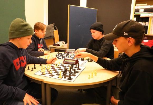 Simon, Theo, Alex och Emil tränar inför Skollags-SM i schack. Lagkompisarna Ellton och Filip är sjuka dagen UBRO kommer på besök.