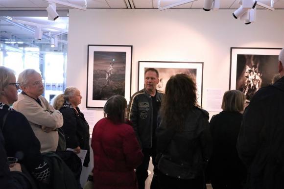 Vernissaget för Brutus Östlings utställning Möten på savannen i Kulturhusets konsthall lockade en månghövdad publik. Här står Östling och berättar om sina möten med lejon.