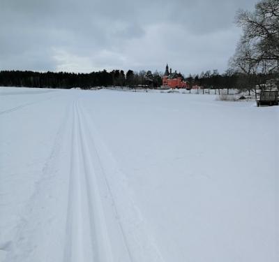 Lejondalssjön och Lejondals slott i Bro. Till vänster i bild skymtar den plogade rundbanan på sjöisen.