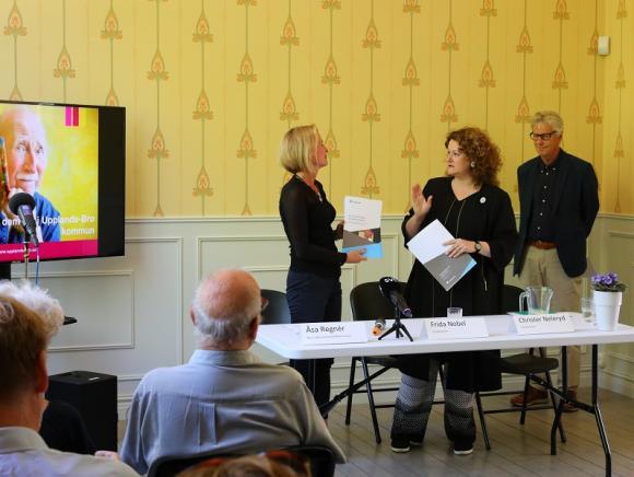 Åsa Regnér är bland annat Sveriges Äldreminister. Här mottar hon utredningen om en nationell strategi för hur man på bästa sätt ska ta hand om människor med demensdiagnos. Frida Nobel och Christer Neleryd har lett utredningsarbetet.