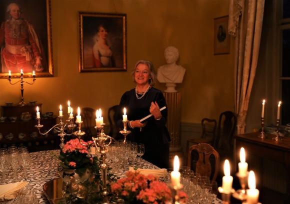 Irène Seth har skrivit bokenAlmare Stäket – en plats, en borg, en gård tillsammans med Dick Harrison samt Lars och Ursula Sjöberg. Här står hon i matsalen som är pyntad och redo för releasefest.
