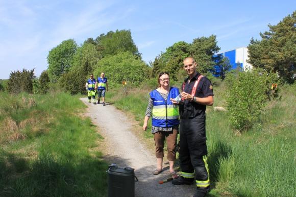 Brandmannen Jakob var törstig. I ett svep försvann en halvliter vatten så det var tur att vi hade med oss stora dunken! I bakgrunden kommer ett gäng som tilldelats uppgiften att hjälpa till med att röja brandgata.
