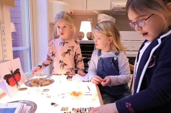 Klara, Molly och Alicia visar hur de kan skapa trumgräshoppor av olika och återvunna material vid ljusbordet.