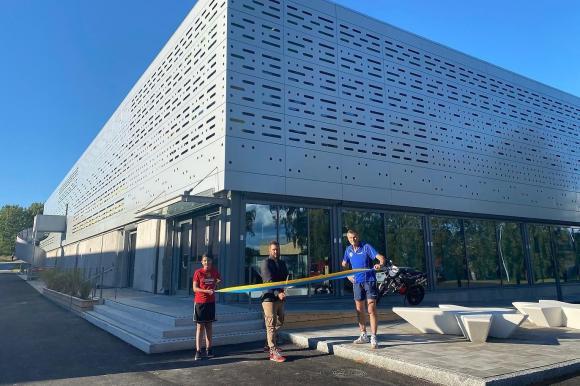 Mattias Peterson (C), ordförande i kultur- och fritidsnämnden, inviger sporthallen i invigningsfilmen. Till vänster, Vera Grobecker från Tibble-Kungsängen BTK och till höger Olle Eklund från Bro IK.