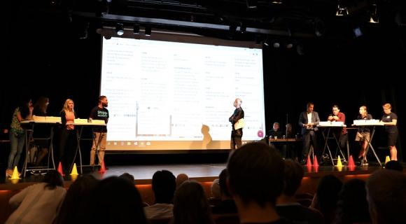 Valdebatt för förstagångsväljare. Fredrik Bergling, moderator, i mitten av bild. Omgiven av åtta partirepresentanter från våra åtta riksdagspartier.