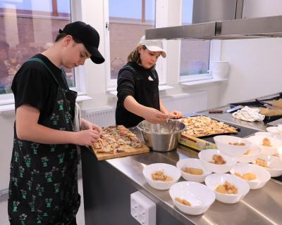 Linus och Elton fixar det sista med renpizzan innan den serveras till skolkamraterna som sitter utanför och väntar.