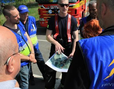 Brandmannen Johan visar eldens spridning på kartan och vart man misstänker att den saknade personen befinner sig. Han pekar också ut var hans törstiga kollegor befinner sig.