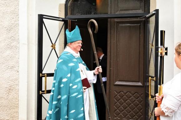 De tre bankningarna gav resultat! Kyrkovaktmästaren öppnade kyrkoporten och släppte in processionen.