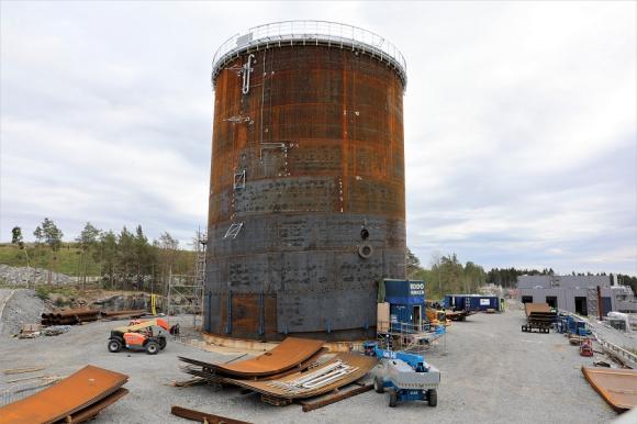 Ackumulatorn växer nerifrån och upp. Redan nu är den imponerande stor, men den kommer att bli mycket högre innan den är klar. Till höger ser ni en mörkblå byggfutt där en byggare är på väg in genom dörren - bara för att få perspektiv på storleken... Ytterligare längre åt höger skymtar den ljusgråa biogasanläggningen som ska invigas den 30 augusti.