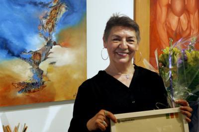Årets Upplands-Brokonstnär Patricia Zuniga framför tavla \