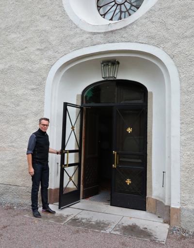 Hans-Cristian Nyström är kyrkoherde i Kungsängens kyrka. Här står han vid den nya fina kyrkoporten. Innanför glasdörrarna finns fortfarande den vackra gamla porten kvar.