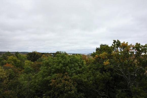 Utsikten från lägenheterna högst upp i några av huskropparna på Bagarvägen. Mälarutsikt! Här i bilden syns även Cooplagret och fotbollshallen. Närmast i bild, bakom alla träd ligger Stationsvägen och tågspåren, vilket knappt syns tack vare träden.