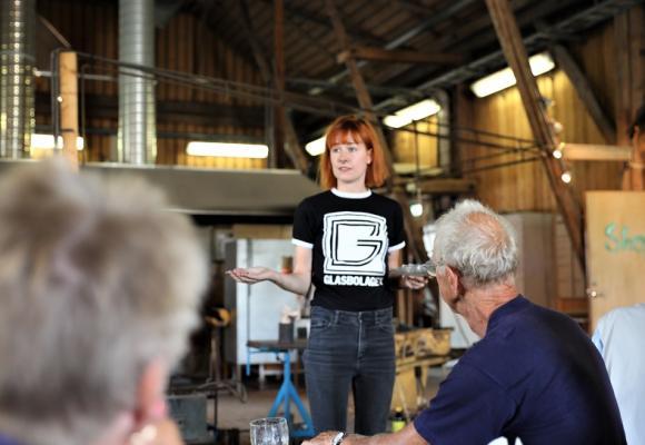 Ammy Olofsson är ena halvan i ägarduon som driver Glasbolaget. Här berättar Ammy om miljötänket på Glasbolaget; att man bara använder återvunnet glas i hyttan som drivs av deponigas från grannen Högbytorp.